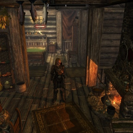 Leona standing in the kitchen to her house, behind her, you can see the bedroom.