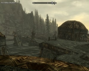 Looking back at the land from the ruins, two sentinels stand broken on the bridge.