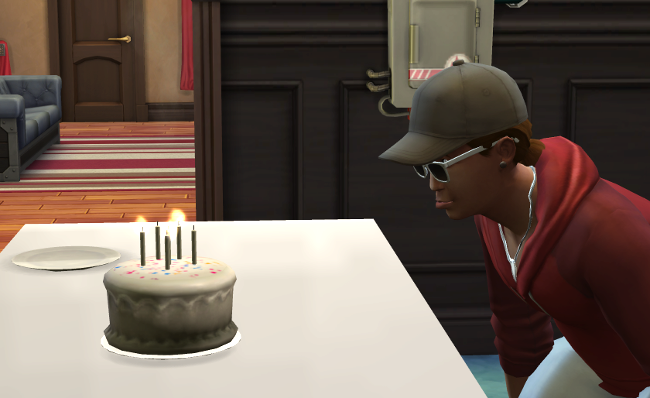 Austin blowing out his candles, bottom lip stuck out in a pout.
