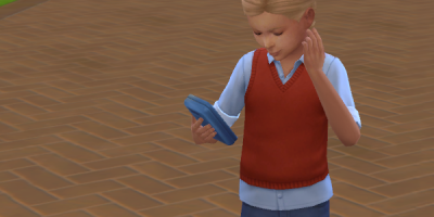 Charlotte is dressed in a sensible red vest and genes, she's looking at her cell phone for some reason.