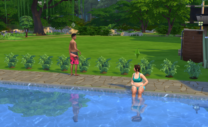 Natasha dangles her feet in the water while Austin tends the garden behind her.