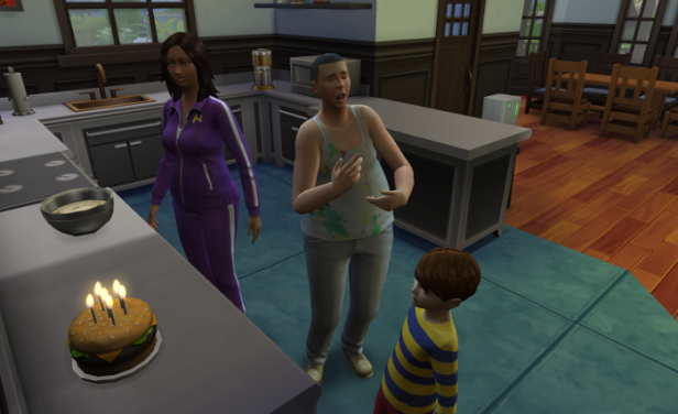 Bourne studies his hamburger cake, while mom and dad smile and watch.