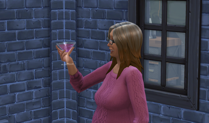 Coral admires her pink cocktail.