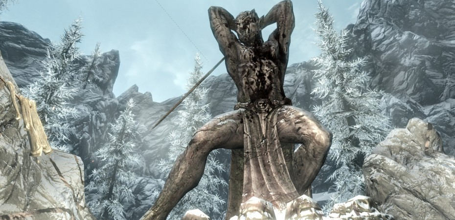 Statue of a warrior orc with a sword, framed by snow-covered pine trees.