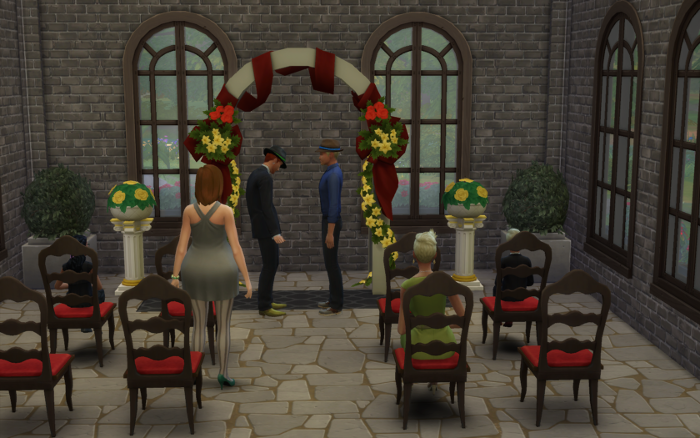 The wedding arch (yellow and red) in a grey stone and brick building (with large windows to give it a chapel feel) and red chairs that most of the guests are using.