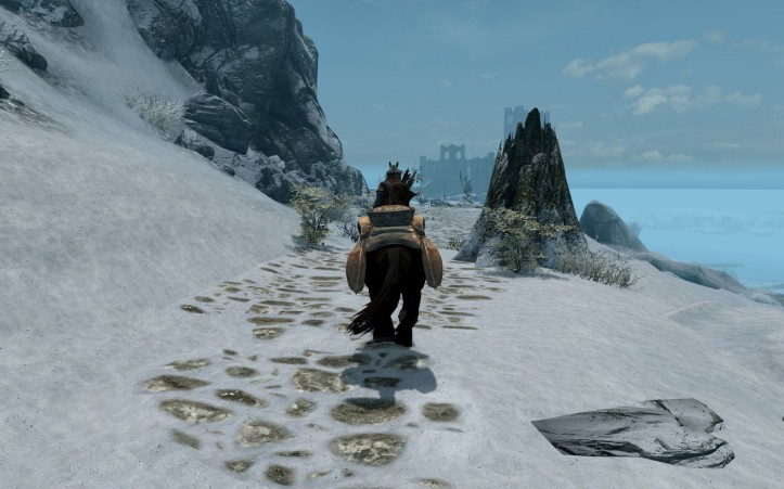 Leona rides down the snowy path, the college of Winterhold looms in the distance.