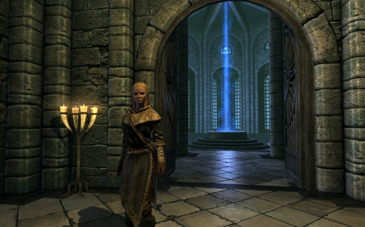 Leona stands in front of the Hall of the Elements, wearing simple mage robes. She looks uneasy.