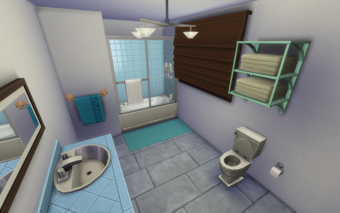 Against the far wall is a white and teal bathtub shower combo, on the the right a toilet and spare towels, on the left double sinks. The room is white and teal and light blue, with a few dark wood accents.