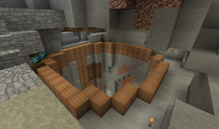 A large hole underground, shored up by wooden beams.