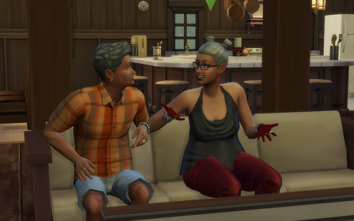 Harley and Michel sit chatting on the couch. The kitchen behind them. Harley is speaking animatedly.
