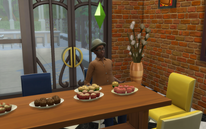 Bane sits down to his exciting mean of Carmel? cupcakes. He looks so happy. (New kitchen BTW, from here on out). The table has five plates of different cupcakes on it.