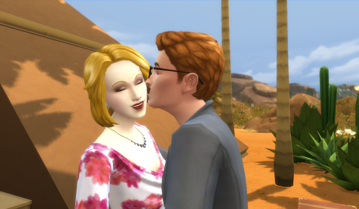 The young man again, he has red hair and glasses, kisses a very blond, very pale woman in a flowery shirt and a pearl necklace. Behind them is a large pyramid shaped building, palm trees, and sand.