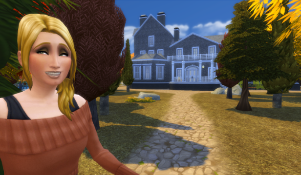 Bridget (blond, long hair, and a big smile looks at the camera. Behind her are trees and a distant Victorian looking building.