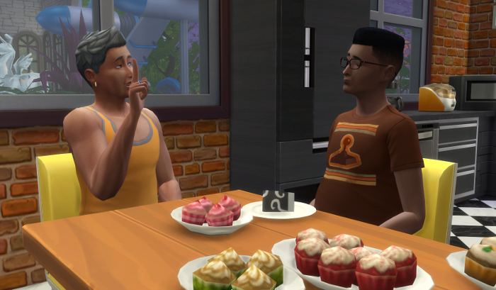 Michel sits down with Bane at the kitchen table (still littered in cupcakes - eat them you sims!) Michel has a finger raised in admonishment.