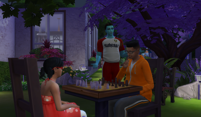 Ari and Bane play chess. Luthor stands nearby in his sports uniform to advise.