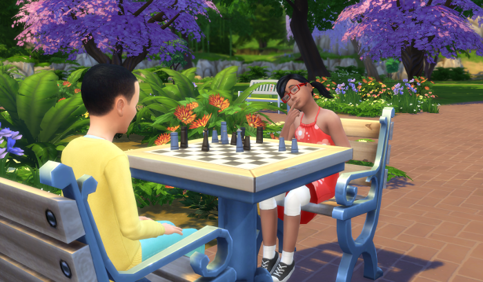 Arianna plays chess at the park with a short haired chile with a yellow sweater.