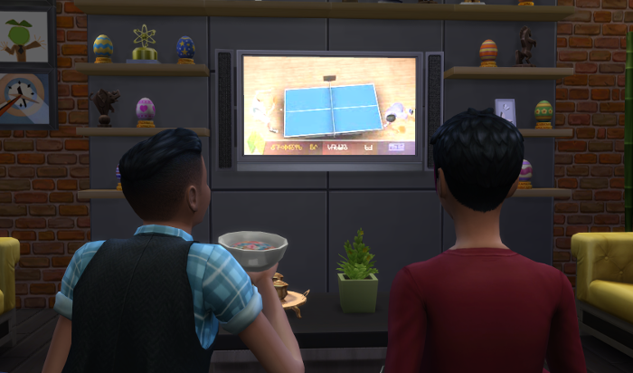 Ari and Hank watch ping pong on TV. Hank is eating cereal.