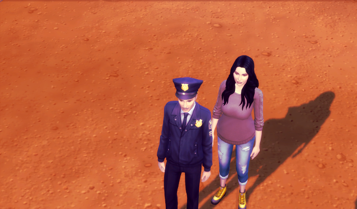 The camera is looking down at two sims in a deserty landscape. one is in a police outfit, the other is in jeans. The color (which is what Adam noticed, is a little redder than normal. All images from Rebirth have this filter applied.