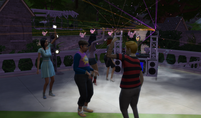 Artruo and Chana and several others (Including Bella and Emeliano) are dancing to the DJ. They are rocking out. Chana has her cellphone lifted for light. Arturo has his fist in the air, all pumped up. Lights and smoke bedazzle.
