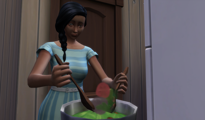 Chana is determinedly mixing a salad with two salad spoons. She in the front hallway cum kitchen.