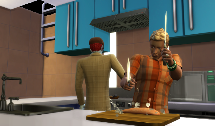 Adam is cooking at the stove, while Michel is chopping up some fish.