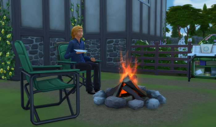 Sam sits in the early morning at the fire outside the house - he is smiling.