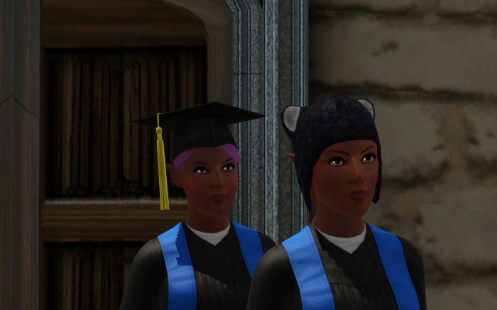 The twins in their graduation outfits, pose in front of the school.