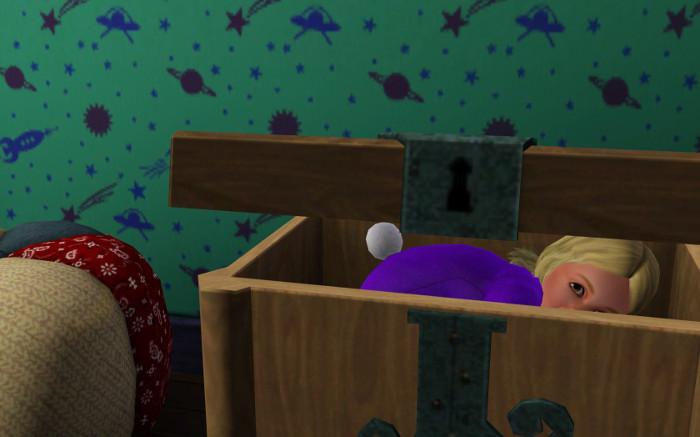 Toddler Fleur hides in a toy box.