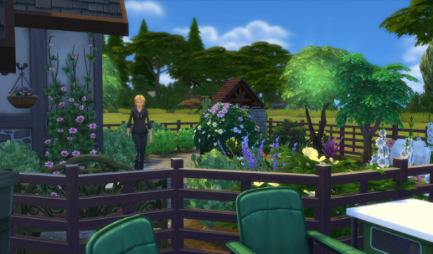 Sam stands in Chana's garden, the flowers and plants look healthy.