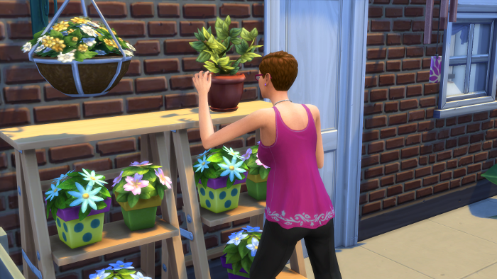 Julia reaches up to carefully tend the death flower outside their tiny brick house.