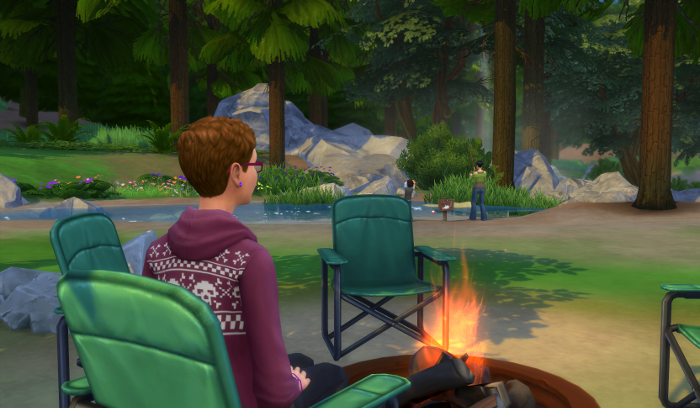 Julia is sitting around the fire. In the distance, Bre and Max are fishing.