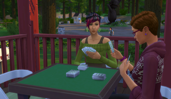 Max is running in the background. In the foreground Julia and Bre are playing cards on the cabin porch.