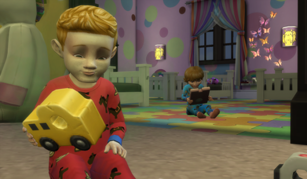 Arturo is in the foreground in red pjs playing with a toy car; behind him sits Sam in blue pjs on the tablet.