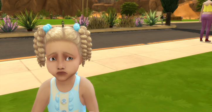 Kierra is a tiny toddler with blond pigtails. She looks like she's about to cry.