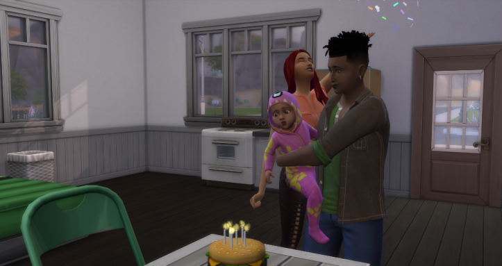 Emery is being held by Skye as she blows out her hamburger cake candles. Behind him Feng (his cousin) is throwing confetti.