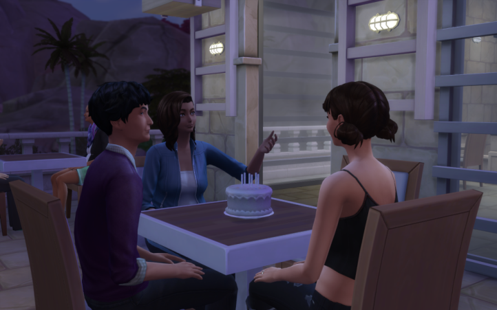 Lane, Evelyn and teenager Abby sit at the patio table, the candles are on the cake, but not lit.