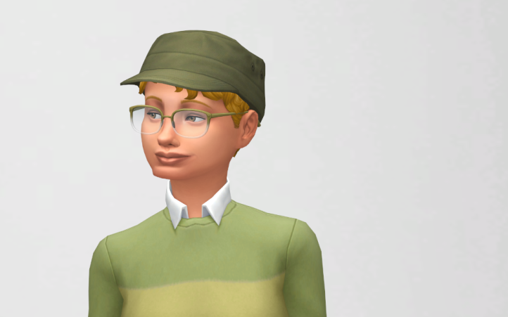 CAS picture of Cora, still with short curly hair, green sweater, cap and glasses.